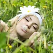 Young woman with flower in her hair blowing on a dandelion. — Stock Photo