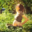 Pregnant woman relaxing on grass in park. — Stock Photo