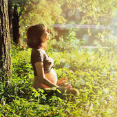 Healthy pregnant woman doing yoga in park. — Stock Photo