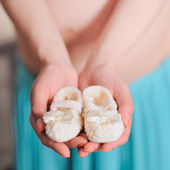 Pregnant belly with newborn baby booties — Stock Photo