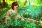 Pregnant woman relaxing on a romantic clearing. — Stock Photo