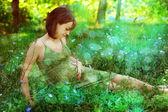 Schwangere frau entspannt auf einer romantischen lichtung. — Stockfoto