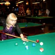 Beautiful woman strikes billiard ball — Stock Photo