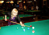 Beautiful woman strikes billiard ball — Photo