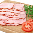 Smoked slices of ham on wooden cutting board - Stock Photo