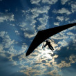 Hang glider silhouette on sky - Stock Photo
