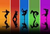 Dancers silhouettes over a rainbow background — Stock Photo