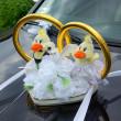 Wedding limousine decorated with flowers and gold rings — Stock Photo