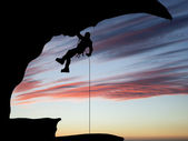 Mountain climber hanging on a rope on the background of sky — Stock Photo