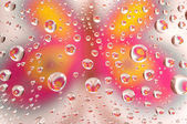 Kropelki wody jako małe soczewki na kolorowym tle. — Zdjęcie stockowe