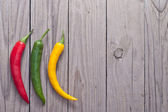 Red, green and yellow hot chili pepper on wooden planks. — Stock Photo