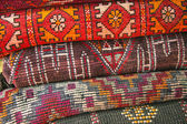 Pile of north african rugs in red, orange & brown shades, Morocc — Stock Photo