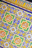Close up of traditional Spanish ornate ceramic wall tiles. Multi coloured with yellows, blues & oranges. — Stock Photo