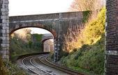 Railway arches over curved rails — Stock Photo