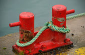 Red Bollards at Harborside with blue ropes — Stock Photo