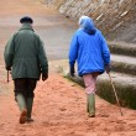 Elderly beach walkers — Stock Photo