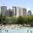 Brisbane skyline and people swimming in the water — Stock Photo