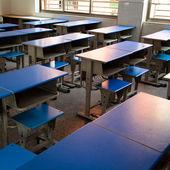 Salle de classe vide avec chaises, un bureau et tableau noir. — Photo