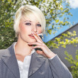 Businesswoman smoking a cigarette outdoor — Stock Photo