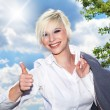 Businesswoman showing OK sign against a cloudy sky — Stock Photo #28450401