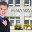 A young businessman on background of building Finanzamt — Stock Photo