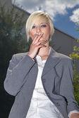 Businesswoman smoking a cigarette outdoor — Stock Photo