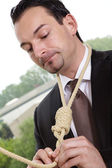 Businessman is hung on a rope — Stock Photo