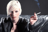 Blonde girl smoking a cigarette on a black couch — Stock Photo