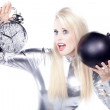 Blonde in a silver dress with an alarm clock and a bomb — Stock Photo