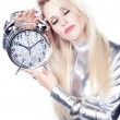 Blonde girl  in a silver dress with an alarm clock — Stock Photo