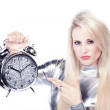 Blonde girl in a silver dress with an alarm clock — Stock Photo #28462249