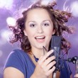 Stock Photo: Girl singing into a microphone