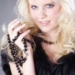 Blonde girl with a necklace in black fur — Stock Photo