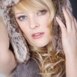 Blonde girl in a fur hat — Stock Photo