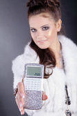 Brunette girl with a calculator in the fur — Stock Photo