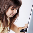 The little girl is considering a magnifying glass laptop keyboard — Stock Photo #28480099