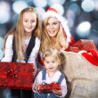 Three happy Christmas girls with gifts — Stock Photo