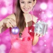 Happy girl with gift and christmas ball in his hands on a bright pink background — Stock Photo