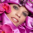 Face of the girl in a pink decorations with orchids — Stock Photo