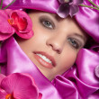 Face of the girl in a pink decorations with orchids — Stock Photo #28485333