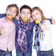 Three boys with apple in mouth — Stock Photo