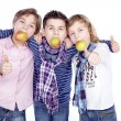 Stock Photo: Three boys with apple in mouth