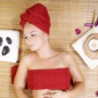 The girl in a red towel lying in massage salon — Stock Photo #28489393