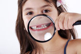Little girl with a magnifying glass — Stock Photo