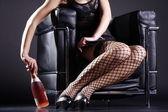 ワインのボトルと革張りの椅子に座っている女の子 — ストック写真
