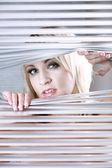 Chica rubia buscando persianas — Foto de Stock
