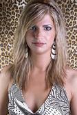 De blond meisje op de achtergrond van een tijger — Stockfoto