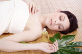 Menina morena relaxa no salão de massagem — Foto Stock
