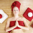 The girl in a red towel lying in massage salon — Stock Photo #28491243