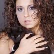 Curly brunette girl with a black cat — Stock Photo